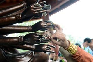 Nhét tiền vào tay Phật có tạo nên phước duyên nơi cửa Phật?